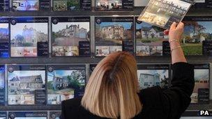 Woman looking in estate agent's window