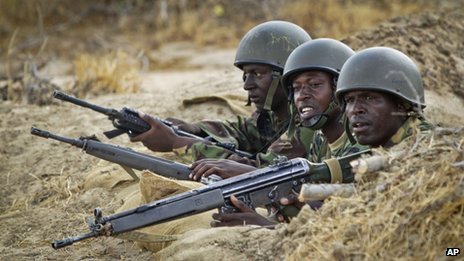 Kenyan army soldiers stand in dugout position at base in Tabda in Somalia on 20 February 2012.