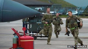 Three men in military uniform running along an RAF runway to a Tornado aircraft