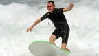 French Catholic priest Rene-Sebastien Fournie surfs at a beach in Bidart, southwestern France, on September 3, 2013