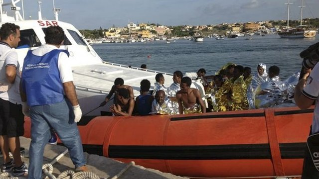 Rescued migrants arrive onboard a coastguard vessel at the harbour of Lampedusa