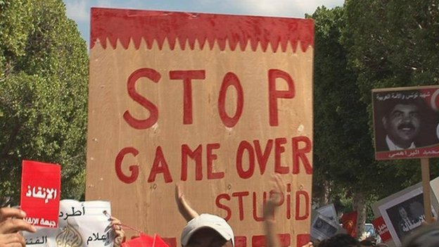 "Slogan on placard in anti-government demonstration in Tunis reading ""Stop, game over."""