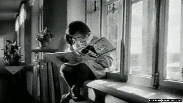 Child sitting on a windowsill, reading a book