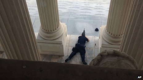 A US Capitol police officer lies on the steps of the Senate with a gun drawn in response to a report of shots fired