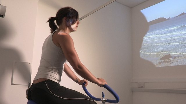 Woman on exercise bike facing a wall with video of the sea projected onto it