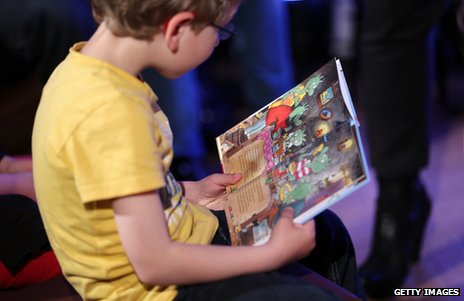 A boy reading an illustrated book