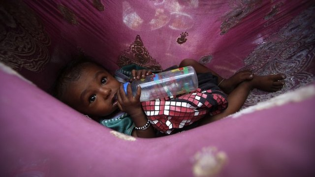Shankar, a six-month-old homeless boy, drinks milk from a bottle as his parents eat their lunch at a street in Mumbai