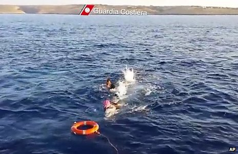 Migrants swim towards a life belt thrown by Italian coast guards, 3 October