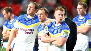 Warrington players commiserate after the defeat by Leeds