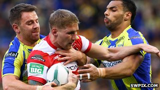 Richie Myler & Ryan Atkins of Warrington tackle Wigan's Sam Tomkins