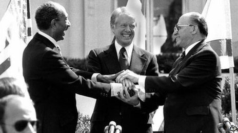 Egyptian President Anwar Sadat, left, US President Jimmy Carter, centre, and Israeli Prime Minister Menachem Begin clasp hands on the north lawn of the White House after signing the peace treaty between Egypt and Israel on 26 March, 1979.