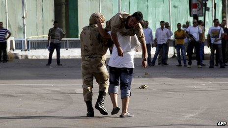 An Egyptian soldier is carried by a comrade and a civilian after he was injured during clashes between supporters and opponents of ousted Egyptian president in the capital Cairo (4 October 2013)