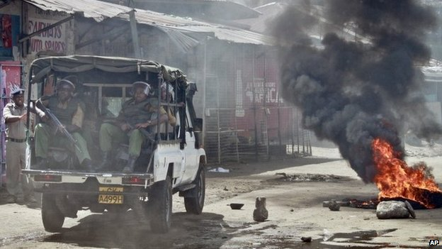 Kenyan security forces patrol in their vehicle past a burning tyre following rioting after Friday Muslim prayers in Mombasa, Kenya Friday 4 October 2013