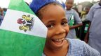 A smiling Nigerian student holding a Nigerian flag in Lagos, Nigeria - Tuesday 1 October 2013