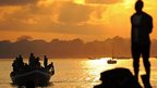 A fisherman looking out at fishing boats as the sun rises in Dar es Salaam, Tanzania - Friday 27 September 2013
