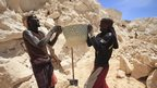 Two men hold up a basket of sand at a quarry on the outskirts of Mogadishu, Somalia - Monday 1 October 2013