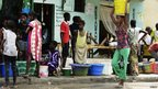 A woman carries a container past people waiting in line to collect water in Dakar, Senegal - 27 September 2013