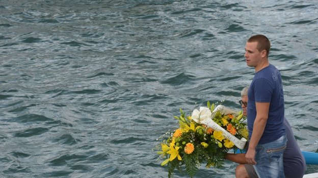 Fishermen prepare to drop flowers in sea near spot where ship sank off Lampedusa, Italy, 5 October