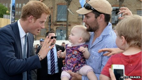 Price Harry greets a baby