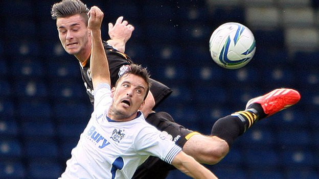 Andrew Hughes of Newport beats Bury's Marco Navas in the air