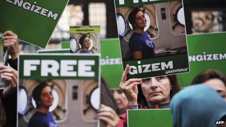 Greenpeace activists hold pictures of their detained colleague Gizem Akhan during a protest in front of the Russian consulate in Istanbul