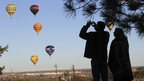 Visitors photograph balloons in the air at the 42nd Albuquerque International Balloon Fiesta.