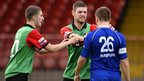 Jim O'Hanlon acts as peacemaker as his Glentoran team-mate Mark Clarke confronts Ryan Harpur of Dungannon Swifts