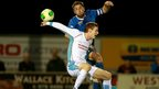 Ballinamallard United skipper Mark Stafford competes for a high ball with Ballymena United opponent Aaron Stewart