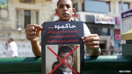 A man carries a poster of ousted Egyptian President Mohammed Morsi, calling for his trial as people gather to mark the 40th anniversary of the Arab-Israeli war