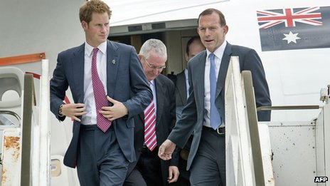 Prince Harry accompanied by Australian prime minister Tony Abbott arrives at Perth airport on 6 October 2013