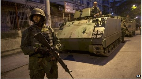 Police before armoured vehicle in Rio de Janeiro