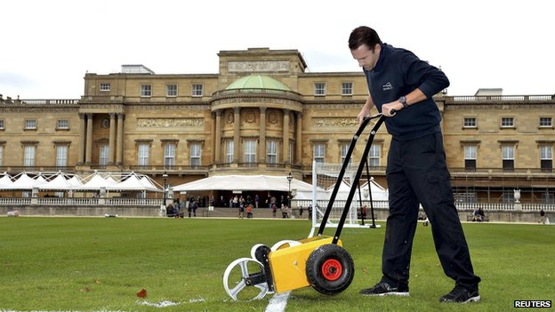 Karl Standley, a groundsman at Wembley Stadium, marks out the the lines of a soccer pitch in the gardens of Buckingham Palace