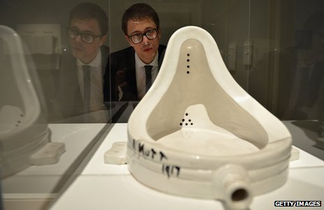 A gallery assistant views Fountain by Marcel Duchamp at The Scottish National Gallery of Modern Art