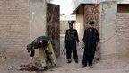 Pakistani policemen stand guard at the site of bomb attack outside a dispensary on the outskirts of Peshawar (7 October 2013)