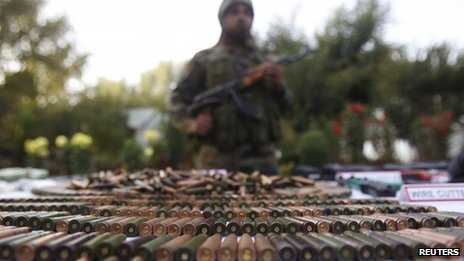 An Indian army soldier stands behind a display of seized arms and ammunition at a garrison in Srinagar,