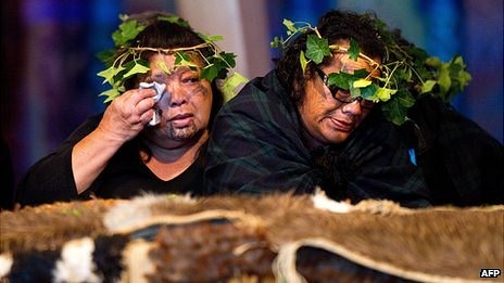 Two members of the Tainui Waka Alliance tribe weep beside the 20 Maori mummified tattooed heads (Toi Moko) returned to New Zealand during a ceremony at Te Papa Museum in Wellington