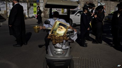 An Israeli man carrying a picture of Rabbi Yosef begs for money during the funeral