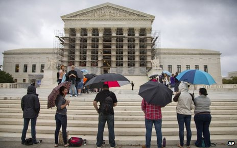 Protesters stand outside the US Supreme Court on 7 October 2013