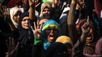 Protesters raise their hands with four-fingers raised and chant in support of Mr Morsi