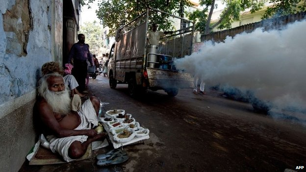 An elderly Indian man sells Ayurvedic medicines at the roadside as a municipal corporation worker fumigates the area to prevent mosquitoes from breeding in New Delhi on September 27, 2013.