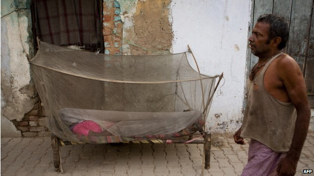 A woman sleeping under a mosquito net in Delhi