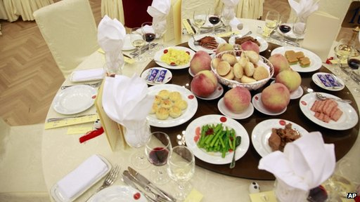 A waitress stand next to a table of food prepared for a National Day reception at the Great Hall of the People on the eve of the Oct. 1 National Day in Beijing