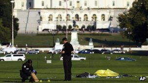 Police investigators gather evidence near where officials said a man set himself on fire, on the National Mall 4 October 2013