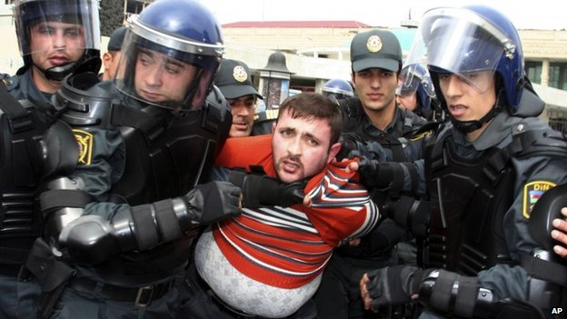 Riot police detain a protester in Baku, 2 April