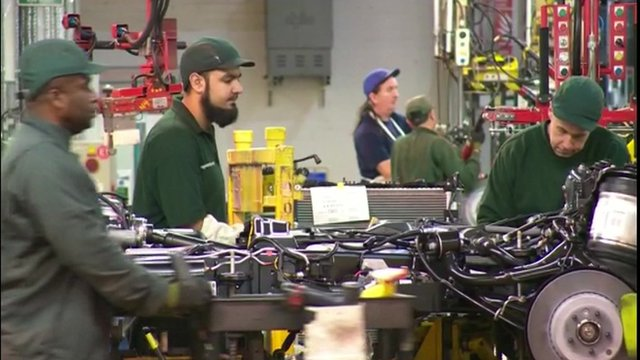 Car manufacturers working in the factory.