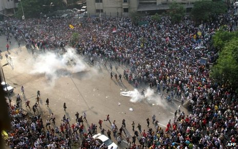 Supporters of Mohammed Morsi run after tear gas is fired at a protest in Cairo (6 October 2013)