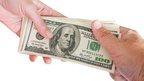 Handing over a pile of $100 bills