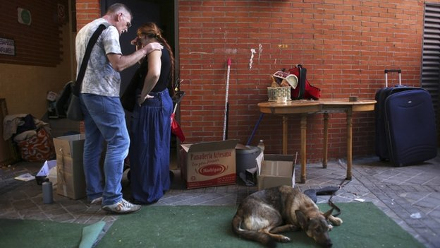 An anti-eviction activist comforts Maria Isabel Rodriguez Romero as she packs her family's belongings outside her apartment, where they had been camping out for a week and a half after their eviction in Madrid, 5 October