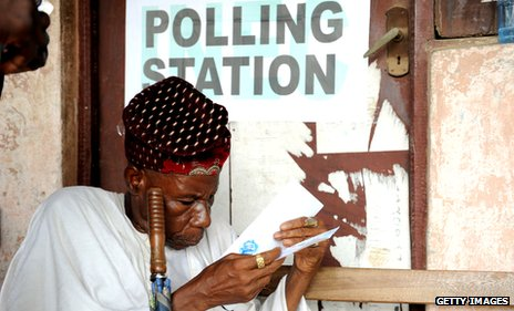 An elderly voter prepares his ballot before casting it at a polling station in April 2011