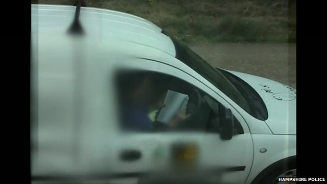 A driver reading behind the wheel